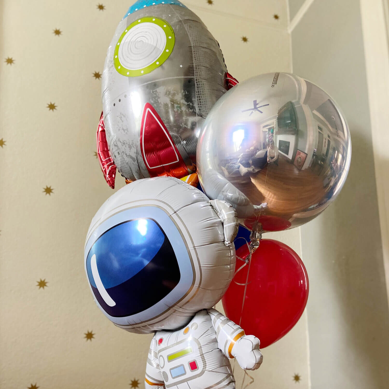 Just Peachy makes oversized helium bouquets like this one with astronaut, rocket ship, and silver orb balloons.