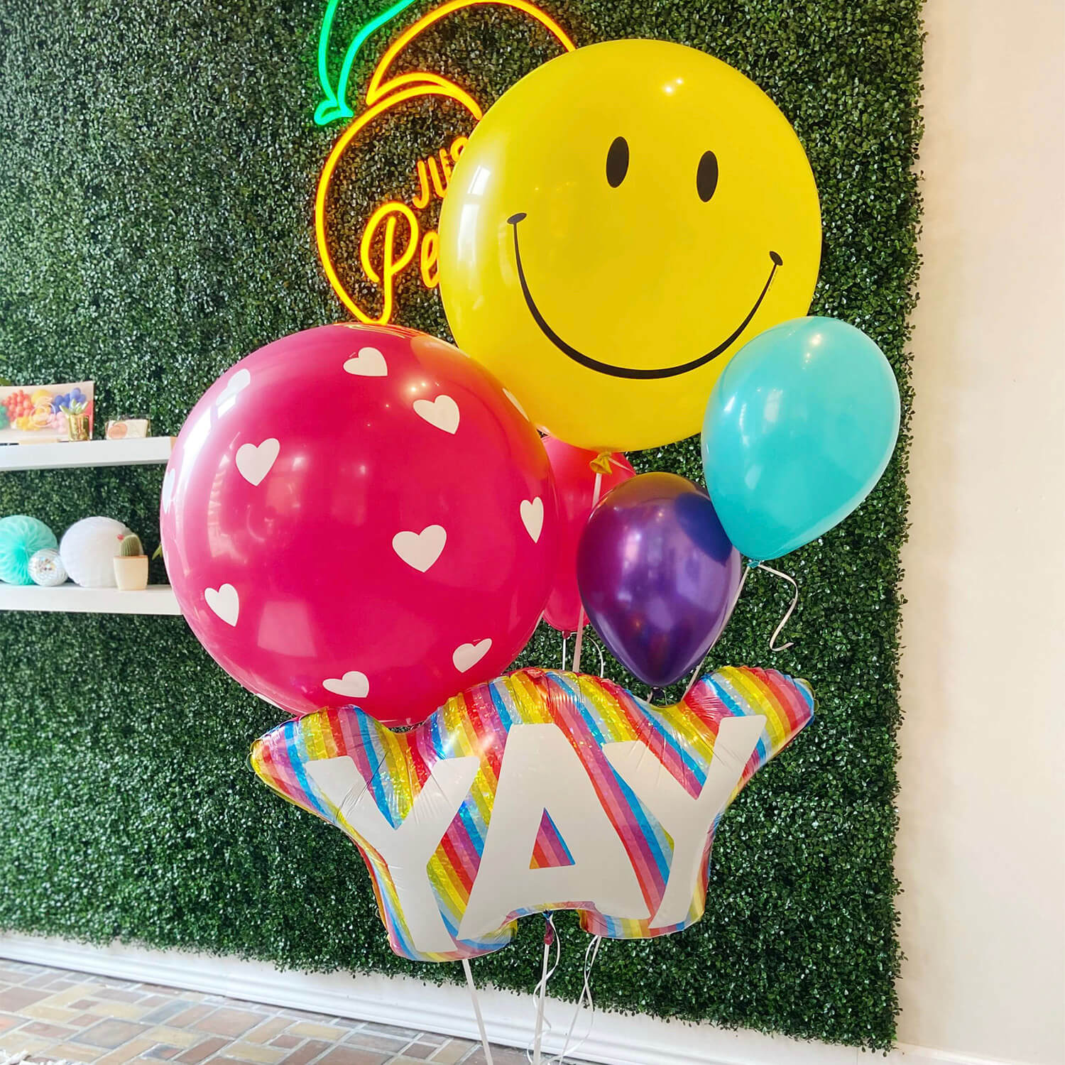 Just Peachy makes giant helium bouquets, like this bundle of a giant smiley face, giant heart balloon, and YAY rainbow lettered balloon.