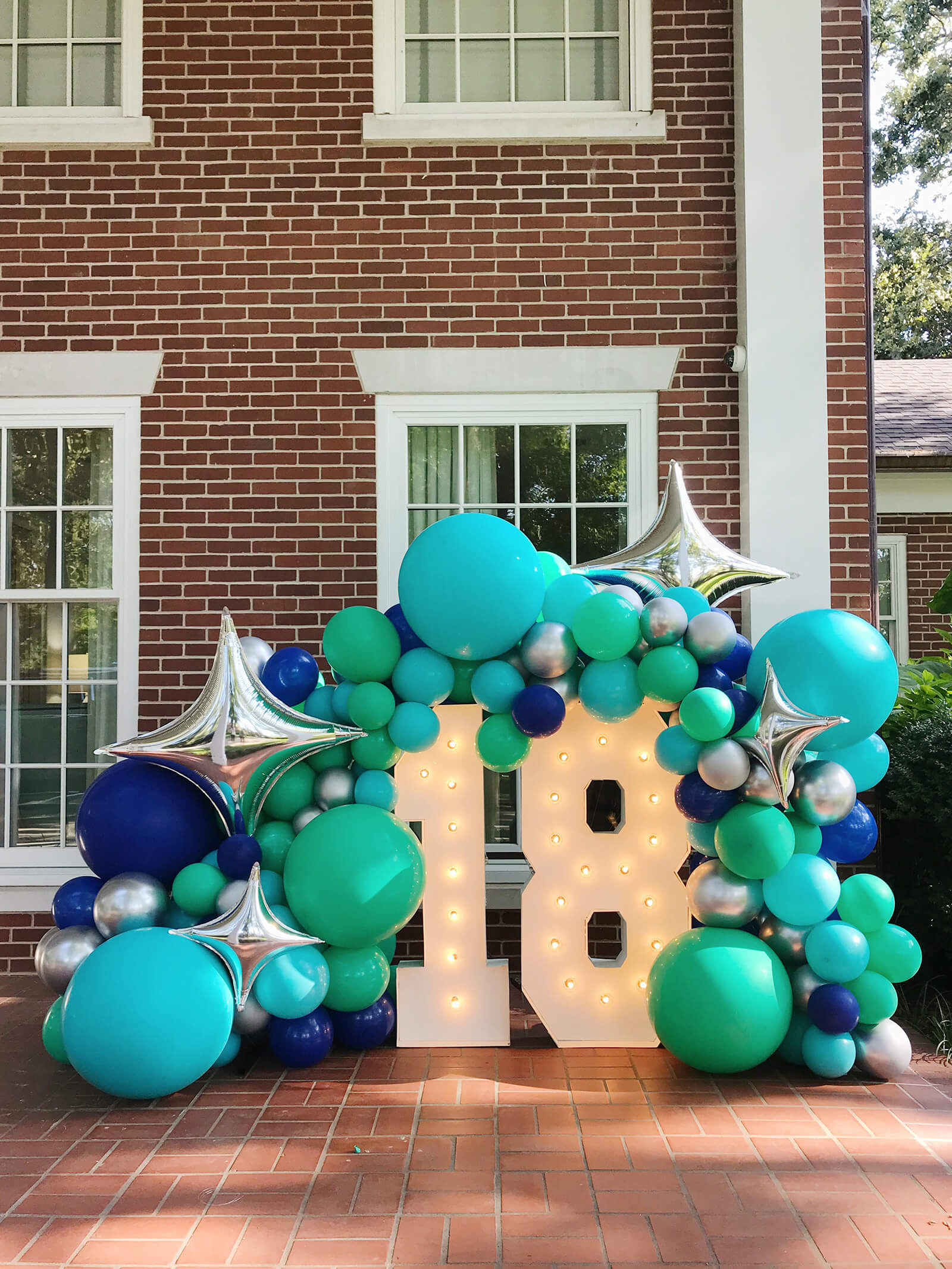 18th birthday front porch celebration; Alpha-Lit marquee numbers with sea blues theme balloon arch installation created by Just Peachy in Little Rock, Arkansas.