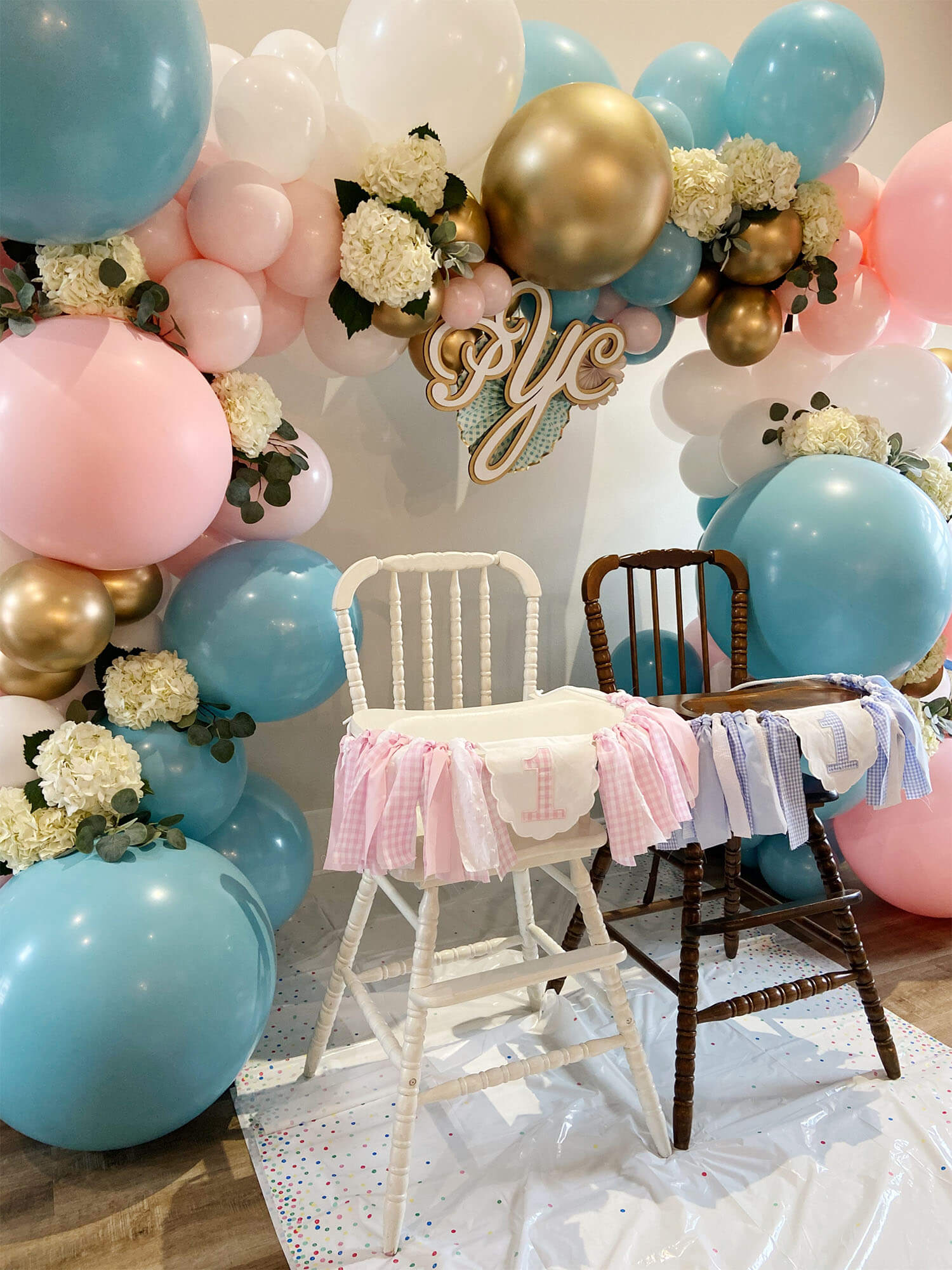 Vintage high chairs with pink and blue balloons and hydrangeas, available from Just Peachy.