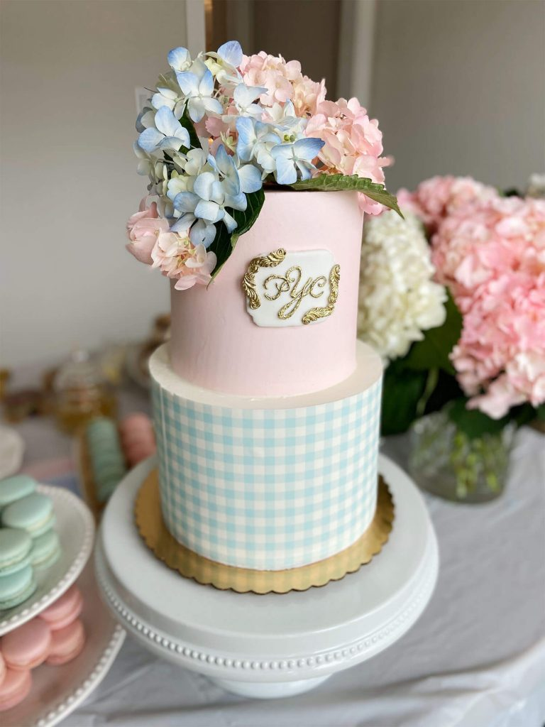 Twins birthday cake with monogram, blue gingham, and pink icing; party planning by Just Peachy.
