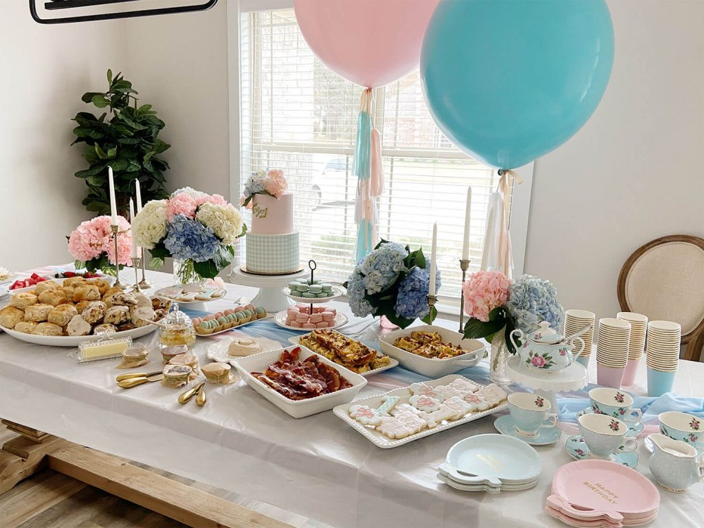 Pink and blue helium balloons behind a first birthday party table; planning and setup by Just Peachy.