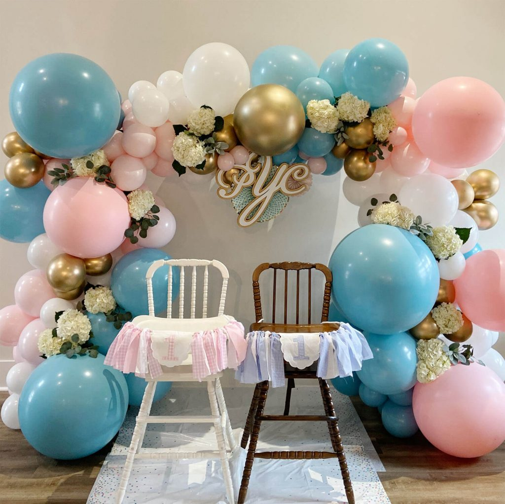 Pink and blue balloons surround two high chairs for a one year old birthday party planned by Just Peachy.