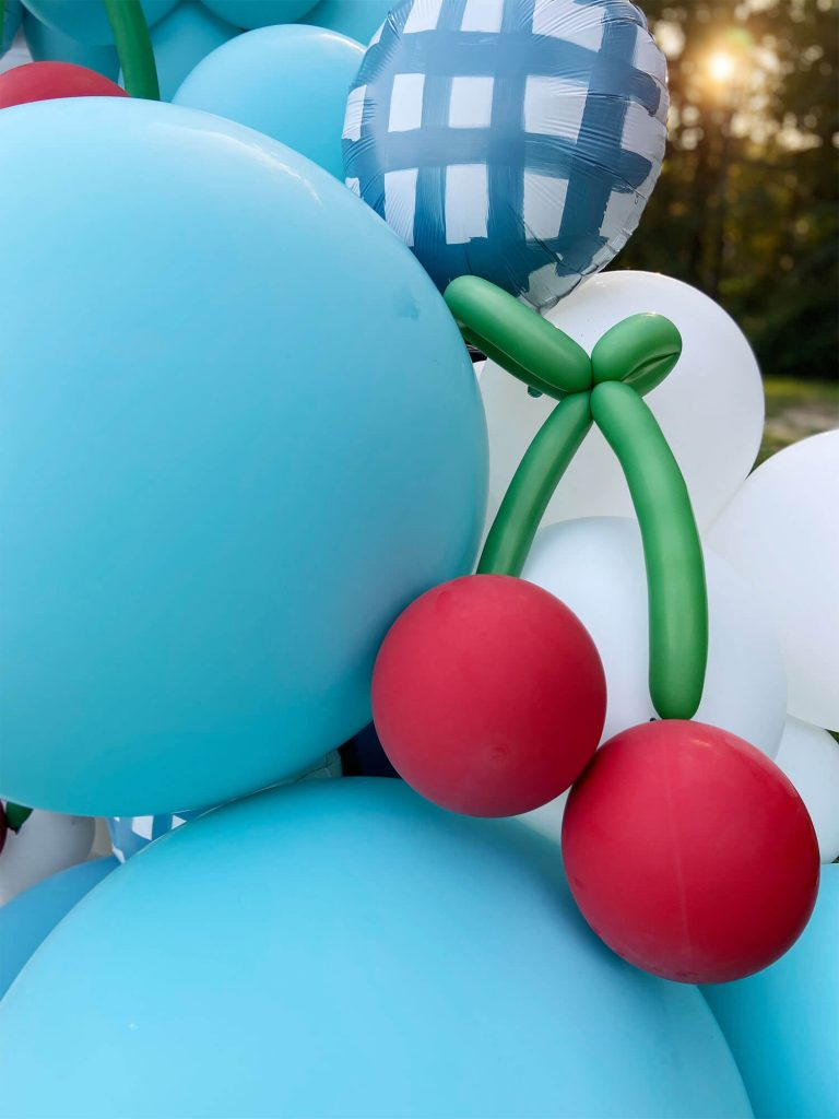 Jumbo blue latex balloons with hand shaped balloon cherries by Just Peachy.