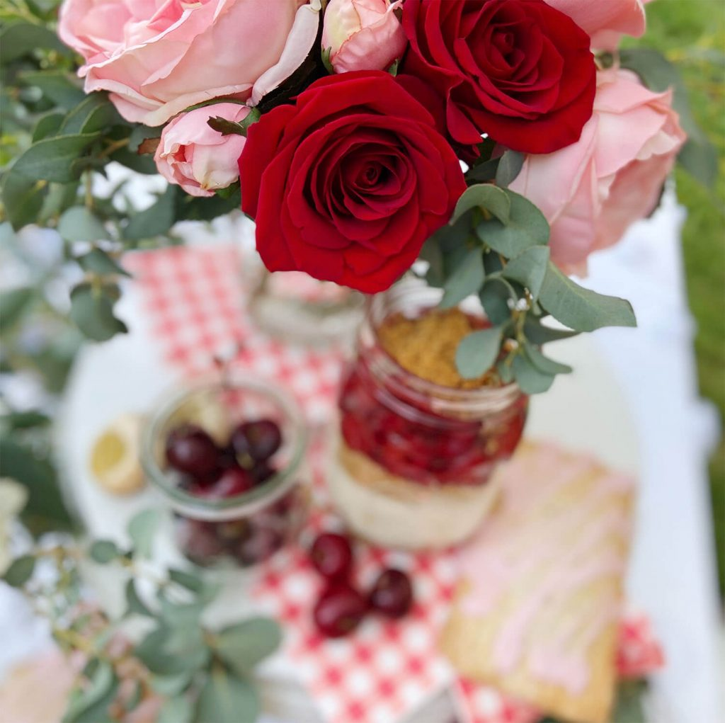 Red and pink roses on a red gingham tablecloth with cheesecake; party styled by Just Peachy.